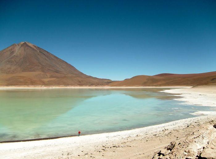 Full length of woman sanding by lake in desert