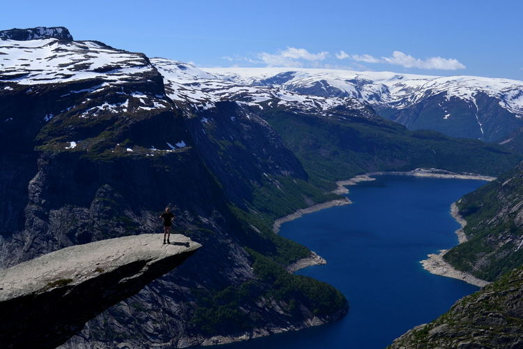 High Angle View Of Person Standing At Trolltunga Against Snowcapped Mountains