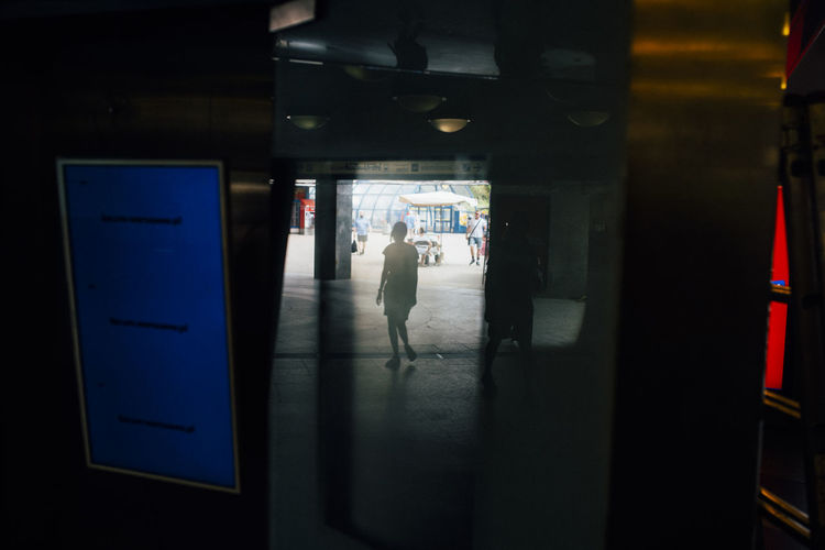 Man and woman walking in illuminated building