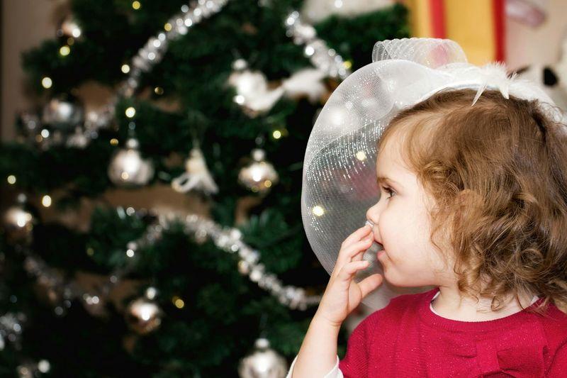 Girl Against Christmas Tree