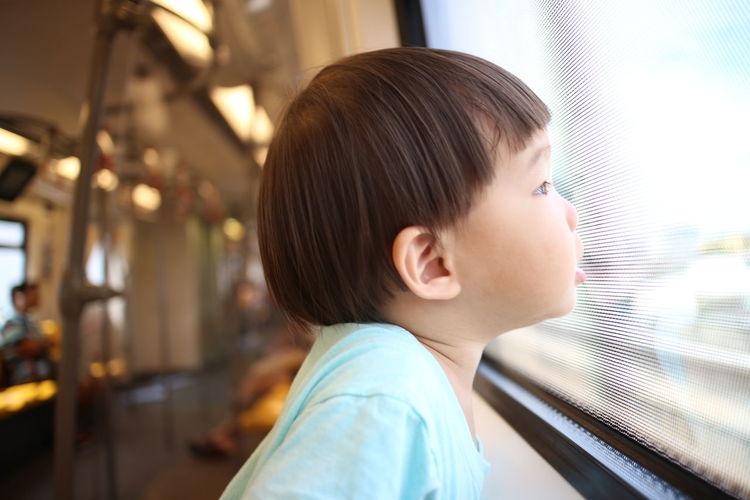 Side view of boy looking through window in train