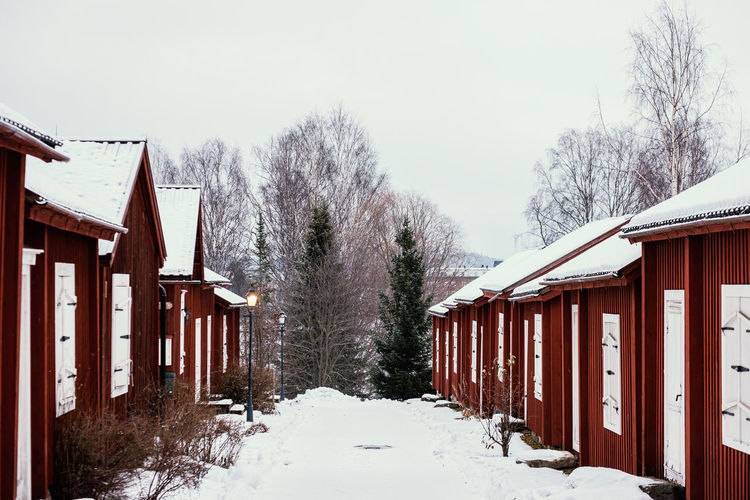 Snow covered houses and trees against clear sky