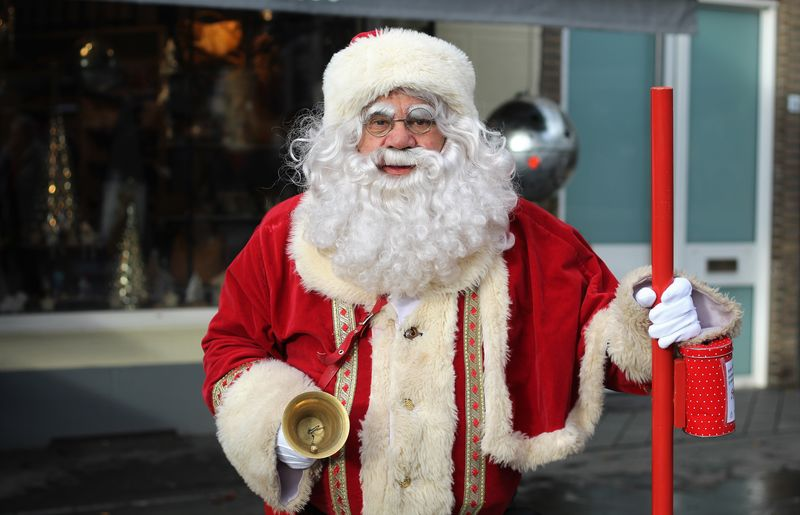 Portrait of senior man wearing santa claus costume while standing outdoors