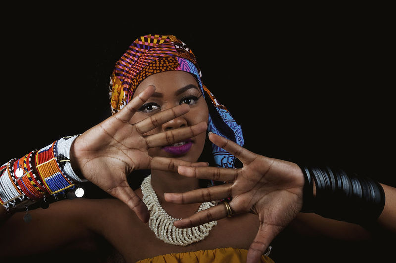 African Woman  Headwrap  African Fabric Accessories Ring Looking At Camera Fingers Palm One Person Human Hand Headshot Front View Portrait Indoors  Hand Human Body Part Lifestyles Studio Shot Black Background Bracelet Real People Body Part Young Adult Adult Emotion Close-up Human Face