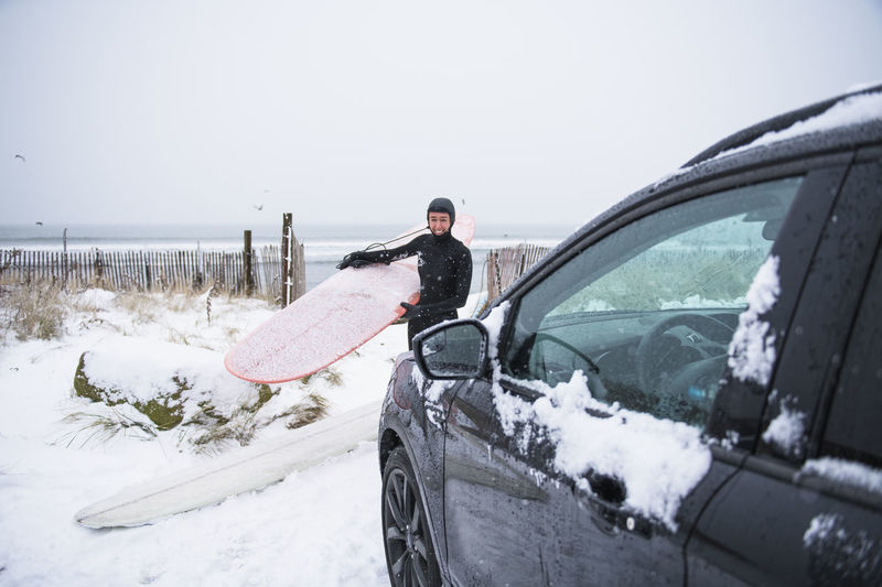 Man in car against sky during winter