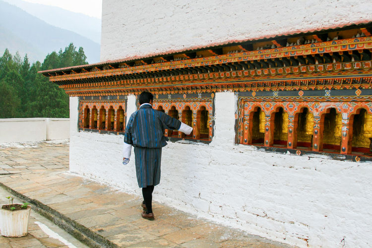Full length rear view of man walking in historical building