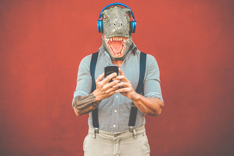 Tattooed man with t-rex mask using smartphone while listening music - Crazy senior guy choosing playlist from mobile phone app - Technology trends and madness costume concept - Focus on face Holding One Person Technology Communication Wireless Technology Studio Shot Copy Space Smart Phone Lifestyles Men Adult Hipster Tattoo Senior Adult Phone Mobile Phone Music Playlist Fashion Trend T Rex  Mask
