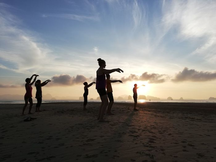Silhouette people exercising at beach against sky during sunset