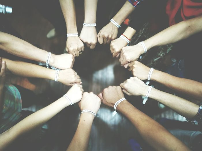 Cropped hands with friendship bracelets forming circle shape