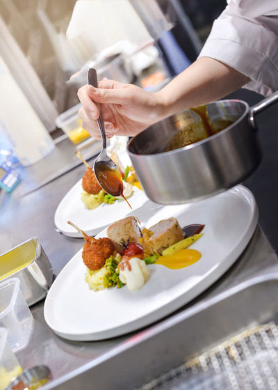Midsection of person preparing food in restaurant