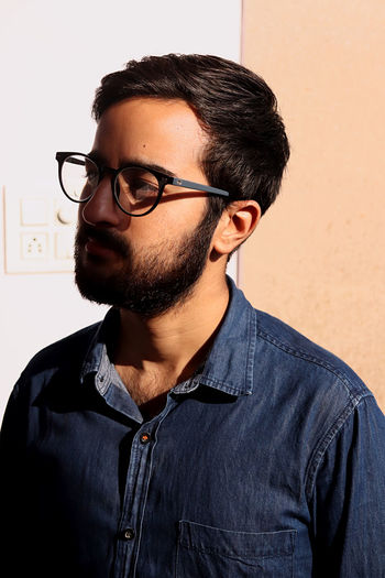 Portrait of young man wearing eyeglasses against wall