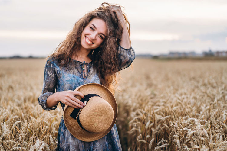 Beautiful young woman standing in a field