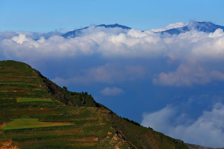 Hui Zher, Between of mountains at Kunming in Yunnan, China Cloud - Sky Sky Scenics - Nature Tranquil Scene Beauty In Nature Tranquility Mountain Non-urban Scene Landscape Environment Nature No People Idyllic Day Green Color Mountain Range Outdoors Grass Land Plant Mountain Peak China