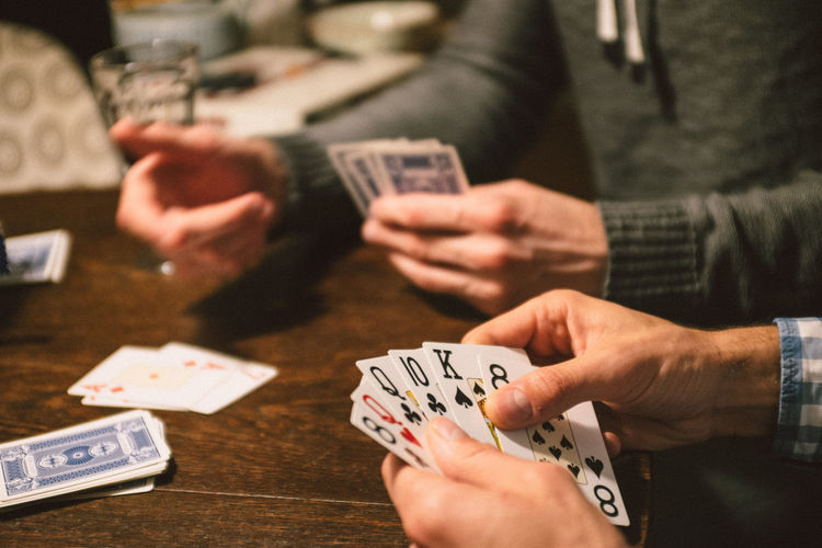 Playing card game with friends Cards Chance Close-up Competition Currency Day Friendship Gambling Gambling Chip Game Of Chance Holding Human Body Part Human Hand Indoors  Leisure Activity Leisure Games Luck Men Opportunity Playing Poker - Card Game Strategy Table Three People Winning