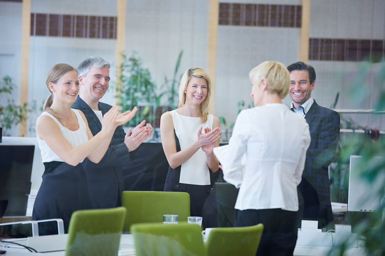Business People Congratulating Colleague While Standing In Office