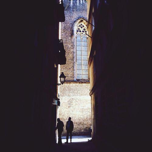 Men standing in passage between buildings
