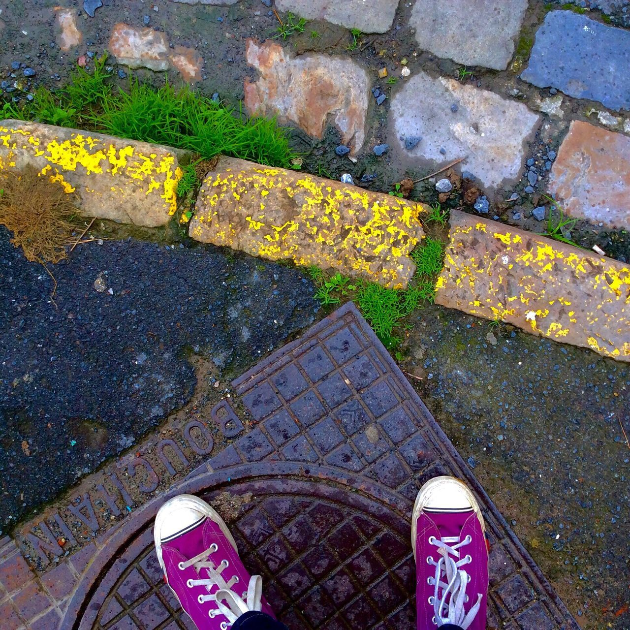 high angle view, shoe, day, outdoors, street, sidewalk, low section, real people, sewage, manhole, one person, gutter, stone tile, standing, puddle, human body part, water, close-up, people
