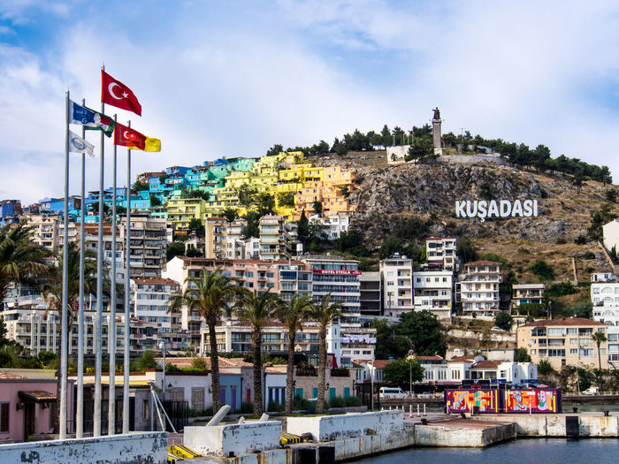 Colourful houses on a hillside overlooking Kusadasi harbour Harbour View Building Cityscape Flags In The Wind  No People Residential District Water Waterfront