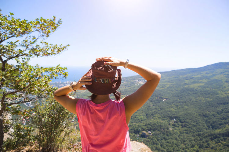 Woman in a hat looks at the panoramic view from the mountain to the sea and the forest. tourist