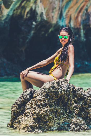 Woman model in a yellow bikini posing on a rock in Maya Bay, Phi Phi Leh, Thailand Beautiful Maya Beach Thai Thailand Beautiful Woman Bikini Fashion Leisure Activity Lifestyles Mermaid Model One Person Outdoors Phi Phi Island Real People Rock Rock - Object Solid Sunglasses Swimwear Water Young Adult Young Women