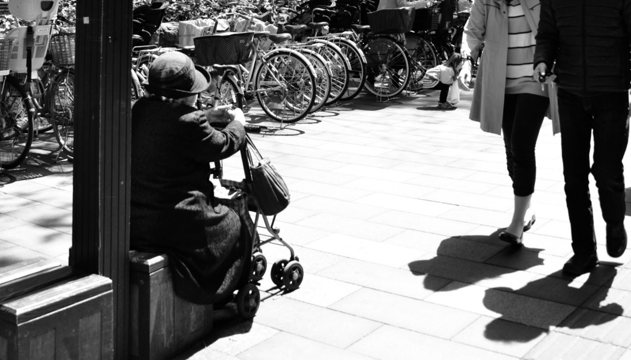 real people, bicycle, lifestyles, one person, transportation, day, land vehicle, full length, men, outdoors, sitting, leisure activity, sunlight, sidewalk, women, mammal, people