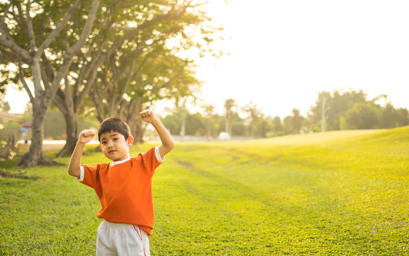 Boy clenching fist while standing on grassy field by trees