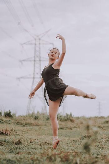 Full length of woman dancing on field against sky