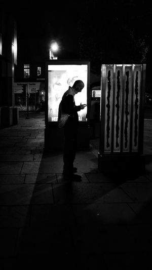 Full length of silhouette man standing on footpath at night