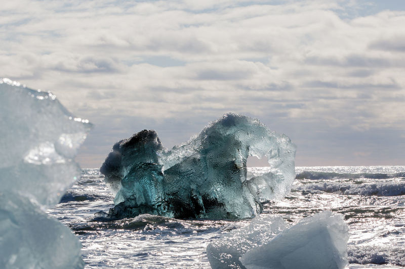 Ice Formations Floating In Sea Against Cloudy Sky