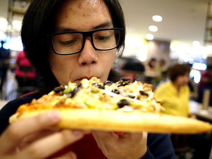 Close-up of teenage boy eating pizza
