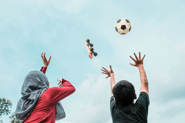 Rear View Of Siblings With Arms Raised Against Skateboard And Soccer Ball In Mid-Air