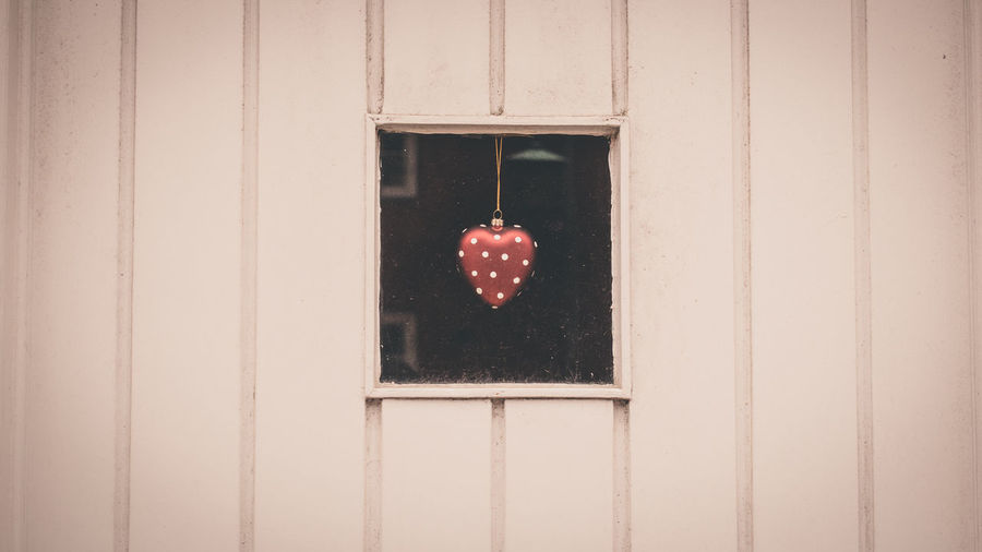Close-up of heart shape seen through window