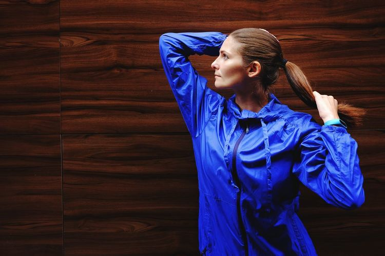 Woman with hand in hair looking away while standing against wall