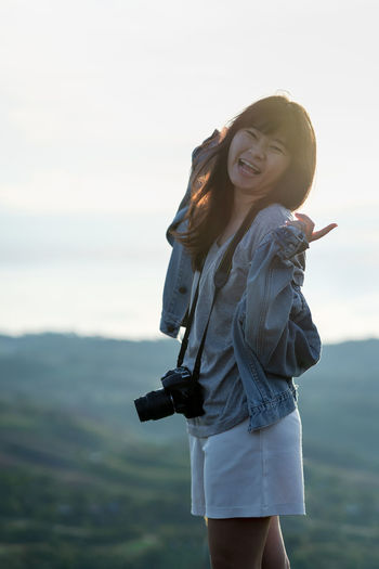 Portrait of pleasant and vivacious Asian woman photographer with jean jacket and camera is raising arm and standing at mountain peak in morning with sunlight and a sea of cloud on vacation. Portrait Nature Outdoors Leisure Feeling Mountain Hill Sunlight Rim Light Young Adult Photographer Travel Traveler Tourism Enjoying Life Happy Happiness Sea Of ​​clouds Smiling Copy Space Good Outstretched Arms Laughing Fun Asian