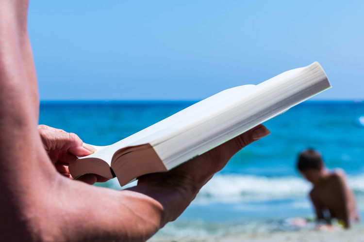 Cropped hands of person holding book at beach against sky