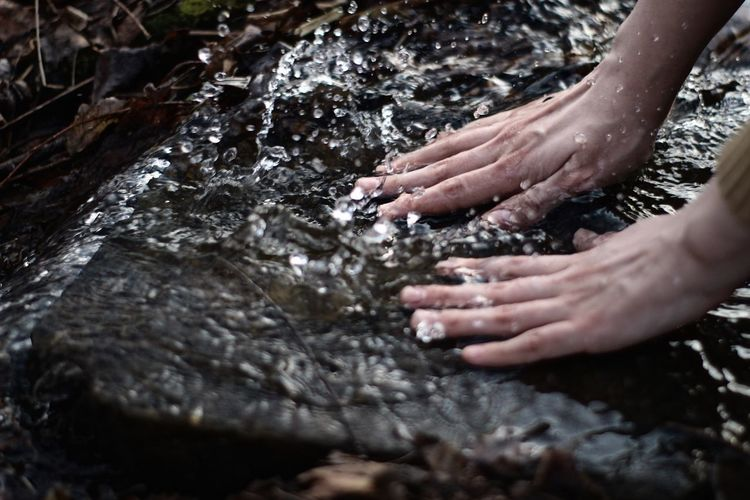 Cropped image of woman washing hands in river