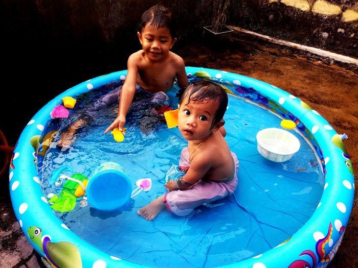 Shirtless Siblings Playing In Wading Pool