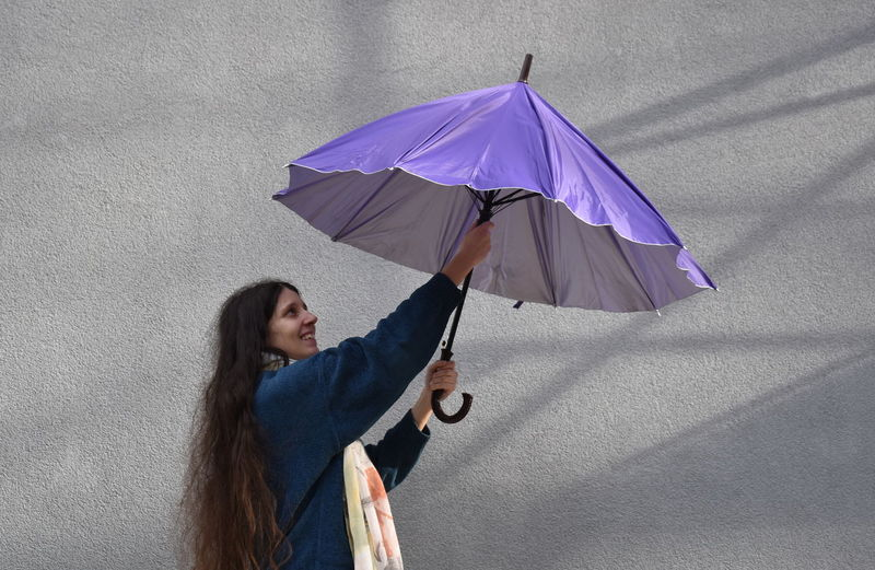 Portrait of the young woman with umbrella on gray background One Person Hairstyle Day Casual Clothing Women Adult Standing Wall - Building Feature Young Adult Lifestyles Looking Leisure Activity Umbrella Gray Background Shadow Scarf Long Hair Violet Smile The Art Of Street Photography The Portraitist - 2019 EyeEm Awards