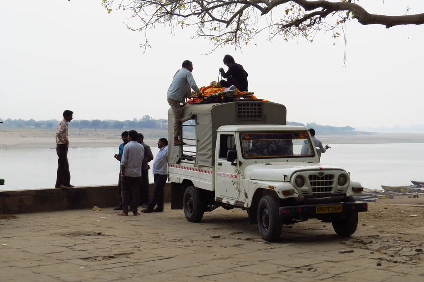 Benares. A dead body did his last journey on the roof top of a 4X4 car. Original death ! And now it will be incinerated on the bank of the holy Ganga River. He is very lucky to get direct to the Paradise ! 4x4 Car Death Ganga Ghat Cadaver Cremation Dead Person Incineration Indian Ceremony Mode Of Transportation