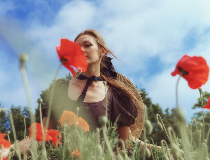 Young woman with red flowers on field against sky