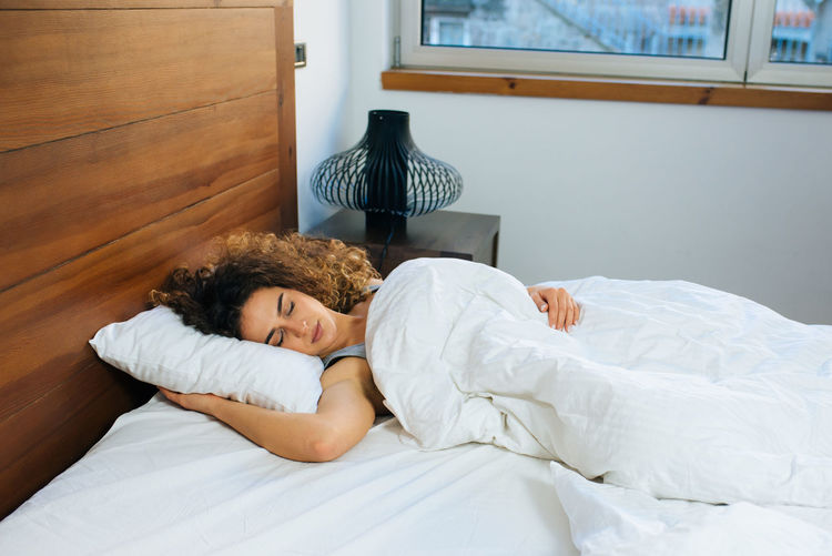 High angle view of young woman sleeping on bed at home
