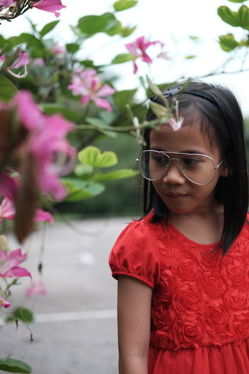 One Person Real People Glasses Plant Girls Females Women Lifestyles Leisure Activity Child Flower Flowering Plant Childhood Looking Eyeglasses  Portrait Focus On Foreground Front View Red Pink Color Outdoors Hairstyle Innocence Contemplation
