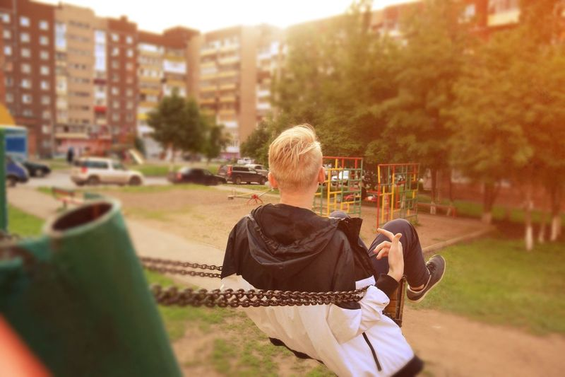 Rear View Of Boy Hanging On Chains At Playground