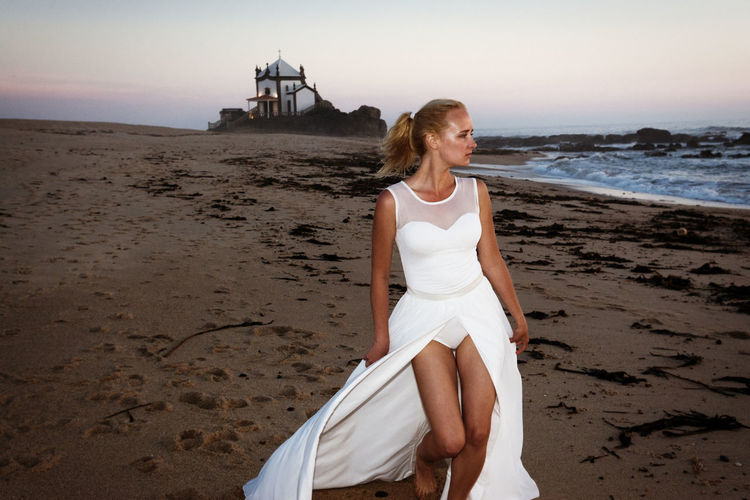 Young woman in white dress walking at beach