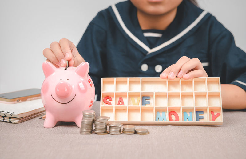 Little girl putting coin into piggy bank for saving with pile of coins on table and show save money
