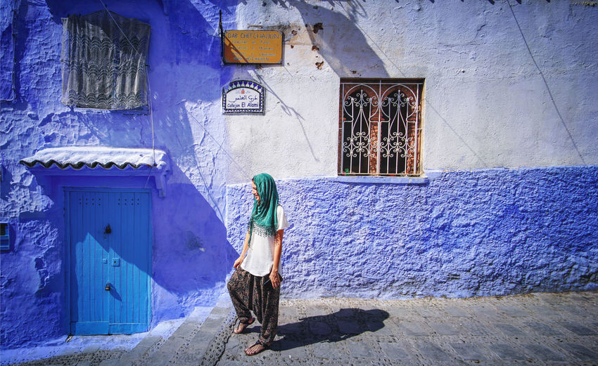 """""""The Blue City"""" We travelled from Sevilla to Tarifa, then took a ferry to Tangier, then a taxi to Chefchaouen, Morocco. EyeEmNewHere a new beginning Chefchaouen Morocco Beauty Blue City Blue Medina Architecture Built Structure Building Exterior One Person Women Lifestyles Day Leisure Activity Outdoors Walking Alley Digital Nomad Real People Wall - Building Feature House Full Length Adult Clothing Rear View Door Building Entrance Warm Clothing"""