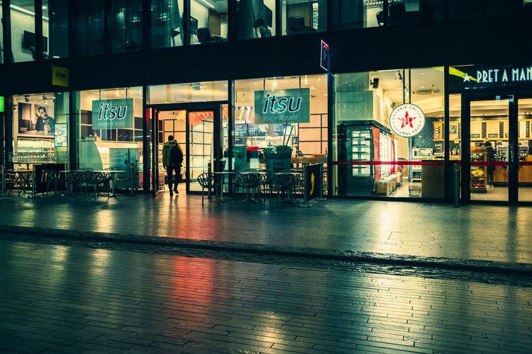 Illuminated text on street in city at night