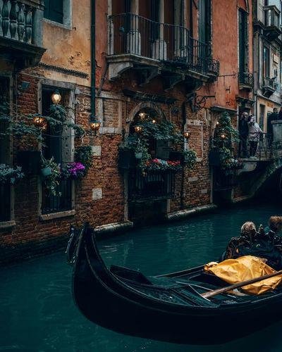 Gondola in canal against buildings