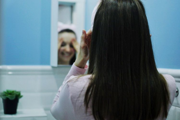 Rear view of woman standing in front of mirror at home