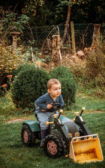 Portrait of boy sitting on plants